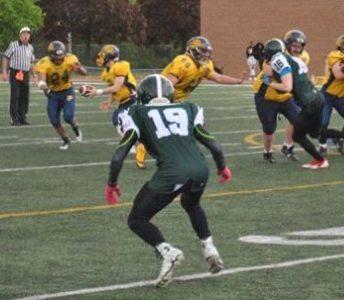 Loic Sogon (#19) defensive back of Etobicoke Eagles looks at opposing running back during a game