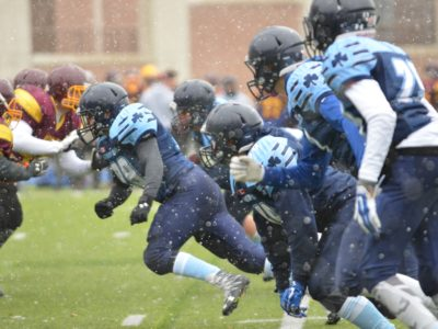 The first player in front (#99) rushing to sack the QB
